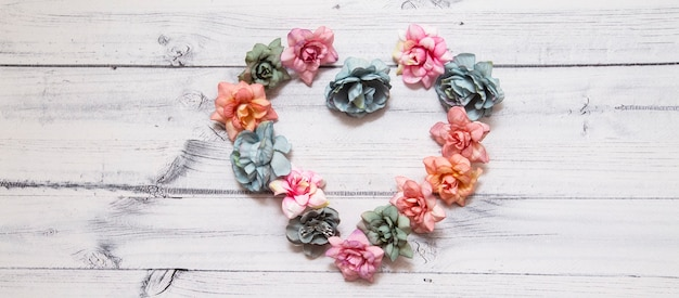 Flowers in the shape of a heart on a wooden background.