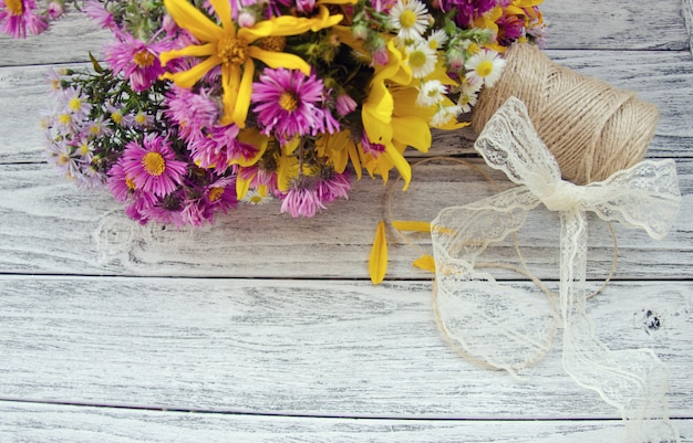 Flowers and a spool of thread on a wooden background
