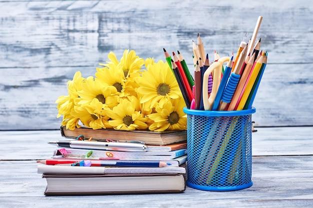 Цветы, канцелярские товары и тетради. знания - это сокровище.