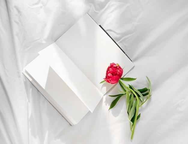花はベッドの中で開いた本にとどまります。ロマンチックなおはようございます。 Premium写真