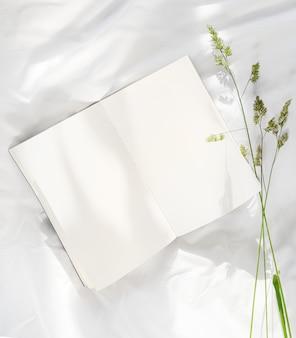 ベッドで開いた本にとどまる花 Premium写真