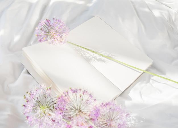 ベッドで開いた本にとどまる花