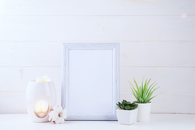 Flowers succulents, candle and aroma lamp with a white frame in the light, copyspace