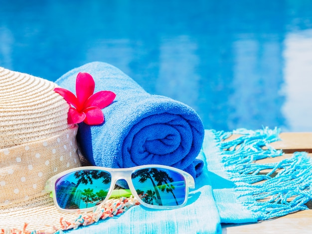 Flowers, sunglasses, beach hat and blue towel at the side of swimming pool.