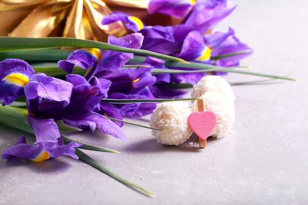 회색 테이블에 꽃, 과자 및 선물 상자