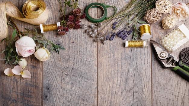 꽃집의 꽃집 테이블에 있는 꽃, 도구, 리본, 장미, 라벤더, 허브, 채소. 나무 소박한 스타일의 테이블, 작업 공간
