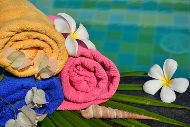 Flowers, towel and water. recreation at the pool. tropical beauty spa. relax and enjoy in the tropics.
