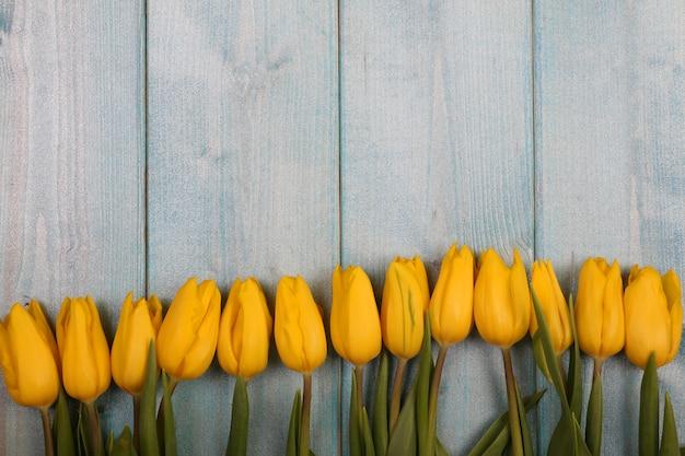 青い木製ヴィンテージテーブルに対して花チューリップフレーム