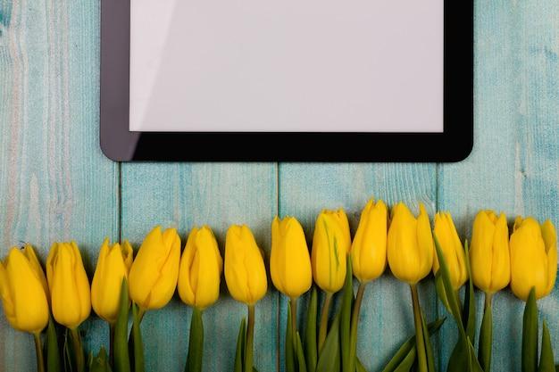 青い木製ヴィンテージテーブルに対してタブレットpcフレームと花チューリップ