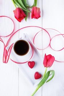 花のチューリップ、ブラックコーヒー、白の2つの赤いキャンディーハート