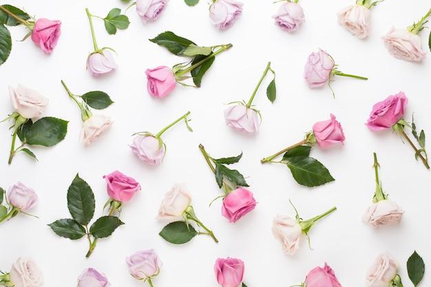 灰色の背景にピンクのバラで作られた花のバレンタインデーの構成。フラットレイ、上面図。