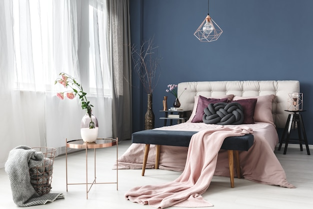 Flowers in vase on small table next to design basket with grey fur in pastel bedroom