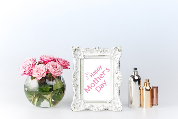 Flowers vase and vintage white picture frame and perfume on white. happy mothers day concept