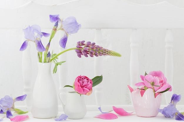 Flowers in vase on white wooden shelf
