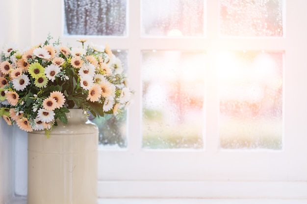 Flowers in vase on window