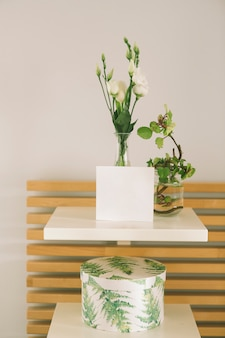 Flowers in vase with blank paper sheet
