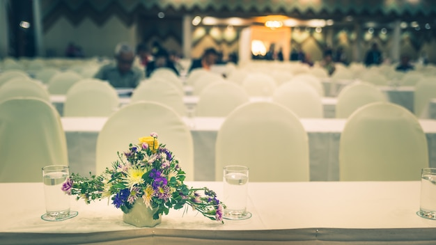 Flowers in vase with blurred meeting room, convention hall defocus abstract and background