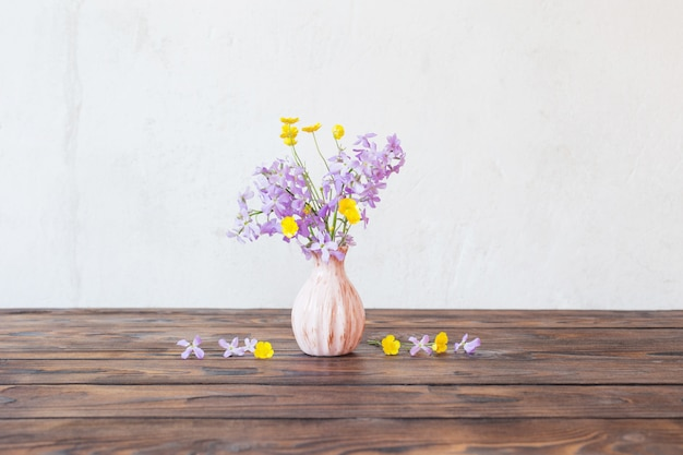 Flowers in vase on wooden table on background white wall