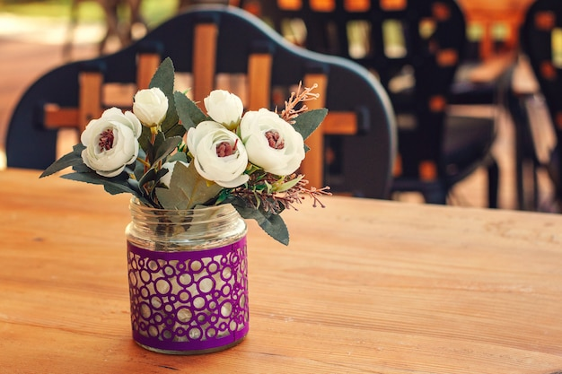 Flowers in a vase on a wooden table in a summer cafe