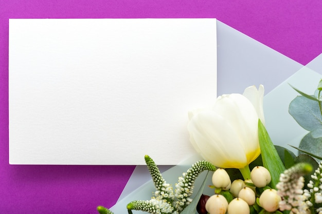 Flowers wedding invitation. congratulations card in bouquet of white flowers tulips, eucalyptus on purple background.