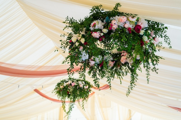 Flowers at a wedding in a tent