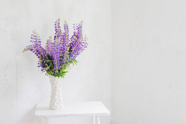 Flowers in white vase in white vintage interior