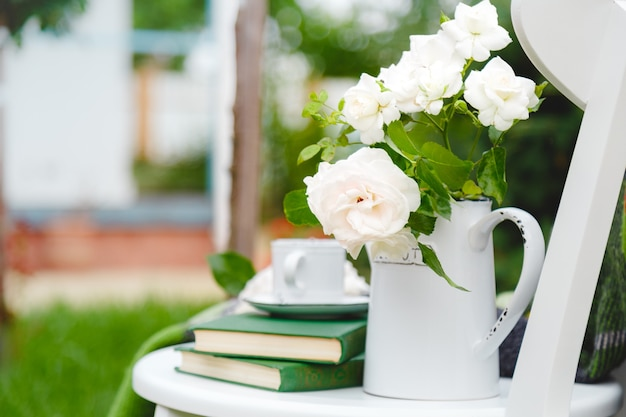 Flowers white wild rose in vase teapot, cup of tea, books on white wooden chair outside in sunny garden. romantic provence leisure breakfast on cozy home terrace with nature background.