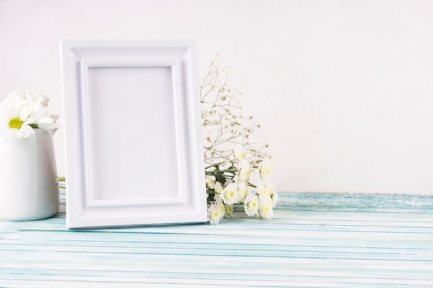 Flowers with blank frame on table