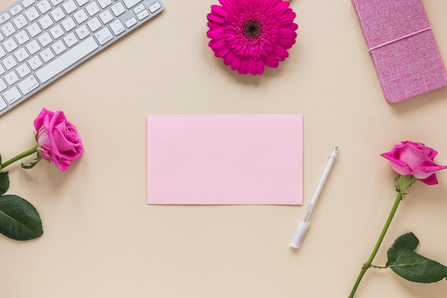 Flowers with blank paper and keyboard