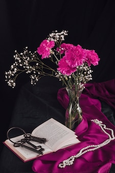 Flowers with bloom twigs in vase near keys on volume and beads on purple textile in darkness