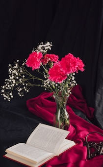 Flowers with bloom twigs in vase near volume and keys on pink textile in darkness