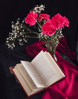Flowers with bloom twigs in vase near volume and rose textile in darkness