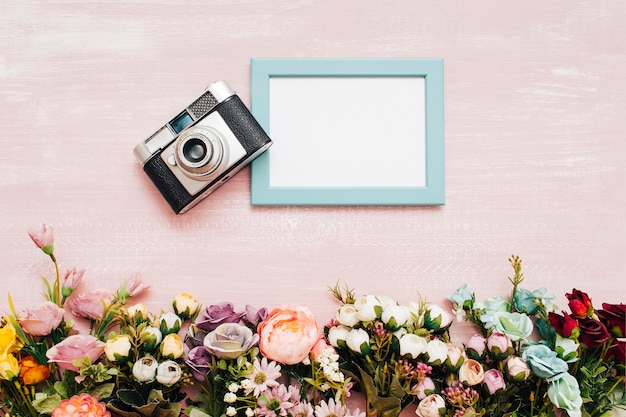 Flowers with blue frame and vintage camera