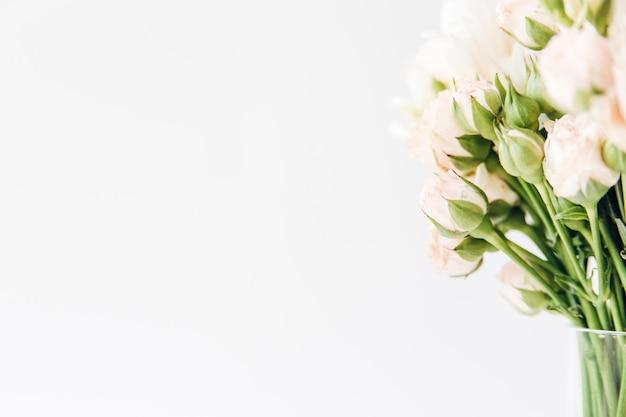 つぼみと緑の葉を持つ花。美しい小さなピンクのバラの最小限のフラットレイ構成
