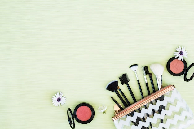 Flowers with makeup brushes and compact face powder on mint green backdrop