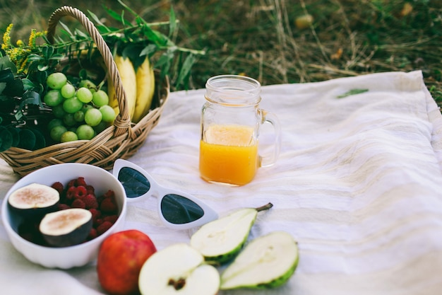 Flowers with picnic fruits in the park. glass with juice and women's glasses and lunch outdoors