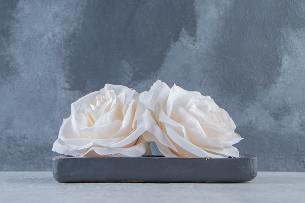 Fiori in un piatto di legno, su fondo bianco. foto di alta qualità