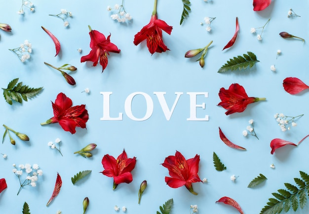 Flowers and word love on a light blue background top view