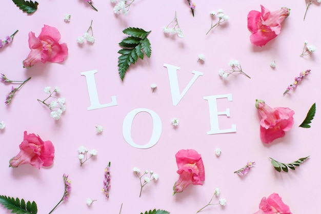 Flowers and word love on a light pink background top view