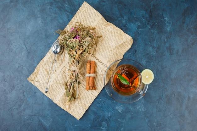 Fiori avvolti in un giornale con una tazza di tè, cannella e un colino da tè tea