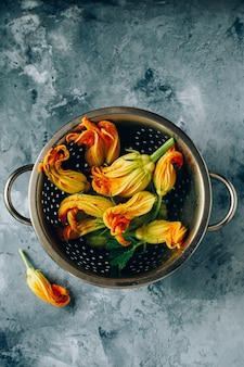 Flowers of zucchini in a colander on the background of concrete