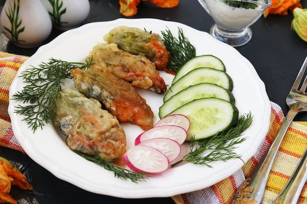 Flowers of zucchini, cooked in batter, slices of cucumbers and radishes on a plate