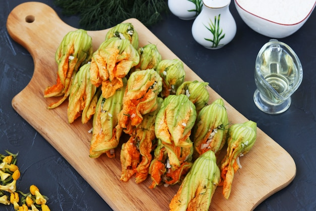 Flowers of zucchini stuffed with cheese are located on a wooden board