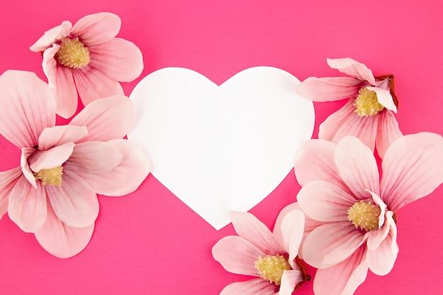 ホワイトペーパーの心とマグノリアflowersoverピンクの背景。