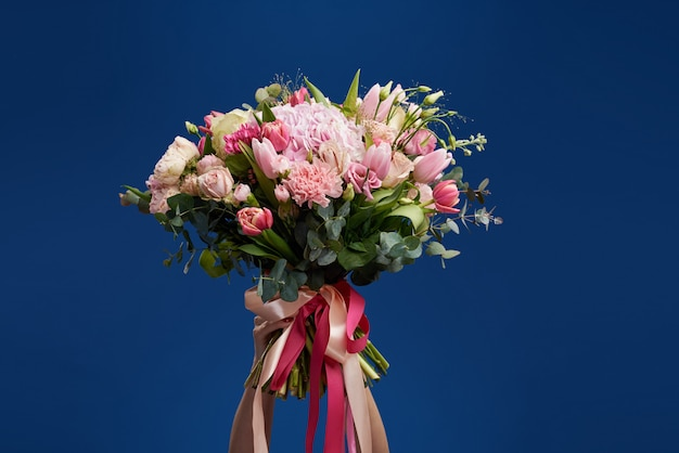 Идеальный подарок. прекрасные цветы в женский день. нежная улыбчивая женщина брюнет держит перед лицом букет весеннего flowerspace для текста