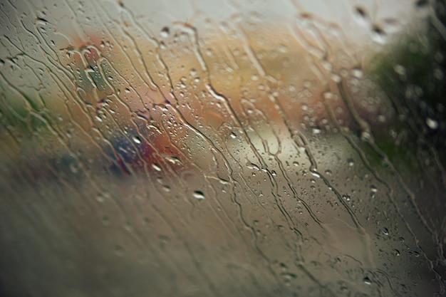 Flowing down raindrops on car window. fall concept.