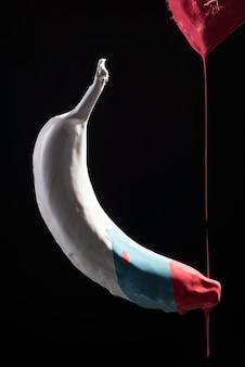 검은 배경에 공중 부양 다색 바나나에 붓에서 빨간 페인트를 아래로 흐르는. 미니멀리즘.