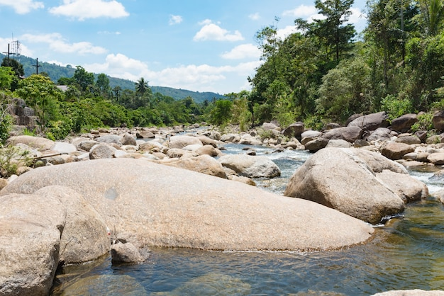 Flowing mountain stream with transparent water and stones