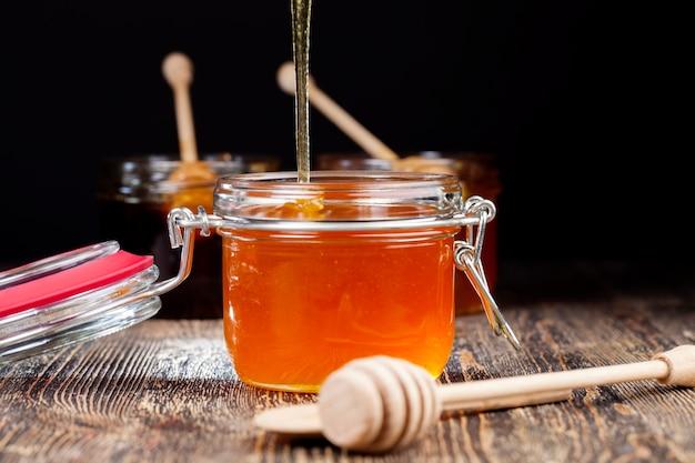 ガラスの瓶に流れる濃厚で美味しい甘い蜂蜜自然で健康的な食品