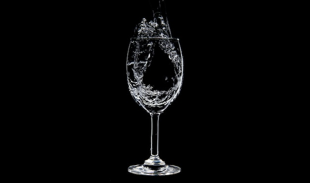 Flowing of water filling into wine glasses